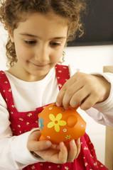 Girl putting a coin into a piggy bank