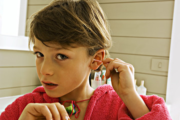 Portrait of a boy cleaning his ear with a cotton swab