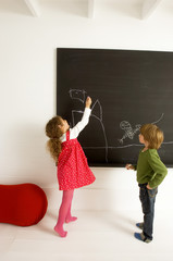 Girl drawing on a blackboard and her brother watching her