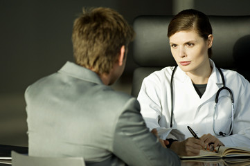 Female doctor sitting at a desk with a male patient in her office