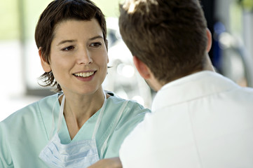 Close-up of a female doctor discussing with a male doctor