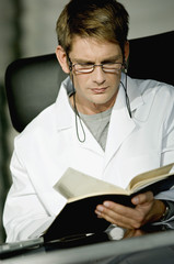 Close-up of a male doctor sitting at a desk and reading a notebook