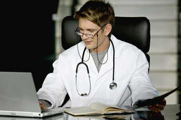 Male doctor working on a laptop in his office