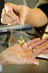Close-up of a woman's hand holding a dowsing pendulum over a woman's palm