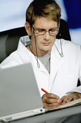 Male doctor sitting at a desk in his office and writing in a notebook