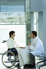Side profile of a male doctor consoling a disabled female patient