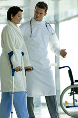 Male doctor assisting a female patient in walking on crutches