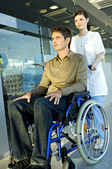 Female doctor pushing a male patient sitting in a wheelchair