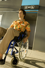 Mid adult man sitting in a wheelchair in front of a restroom entrance
