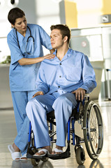 Male patient sitting in a wheelchair and a female doctor standing beside him