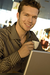 Portrait of a businessman holding a tea cup in front of a laptop