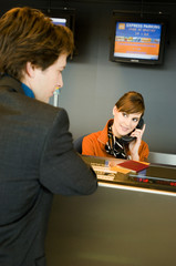 Businessman standing at an airport check-in counter while the check-in attendant talking on the telephone