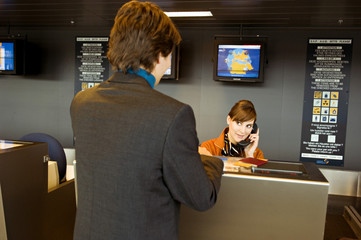 Rear view of a businessman standing at an airport check-in counter and the check-in attendant talking on the telephone