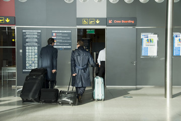 Pilots with luggage at airport, rear view