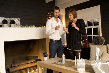 Mid adult man and a young woman lighting a candle with a cigarette lighter