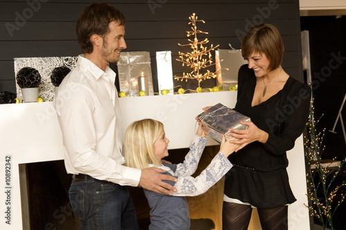Girl giving a Christmas present to her mother with father standing behind her