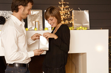 Side profile of a mid adult man giving a Christmas present to his wife