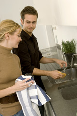 Young man helping a young woman in the domestic kitchen