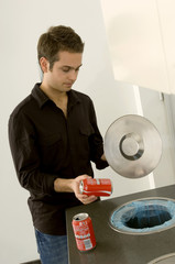 Young man putting a drink can in a garbage bin