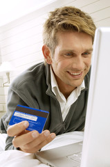Mid adult man working on a laptop and holding a credit card