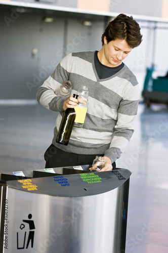 Mid adult man putting empty bottles into a garbage bin