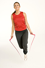 Portrait of a young woman skipping with a jump rope
