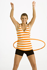 Portrait of a young woman spinning plastic hoop around her waist