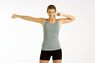 Portrait of a young woman exercising with dumbbells