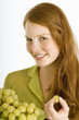 Portrait of a young woman eating grapes and smiling