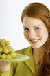 Portrait of a young woman holding a plate of grapes and smiling