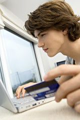 Close-up of a teenage boy using a laptop and holding a credit card