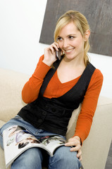 Young woman sitting on a couch and talking on a mobile phone