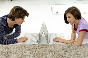 Side profile of a teenage boy and a young woman using laptops
