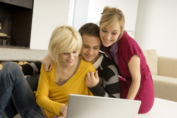 Young man with two young women looking at a laptop and smiling