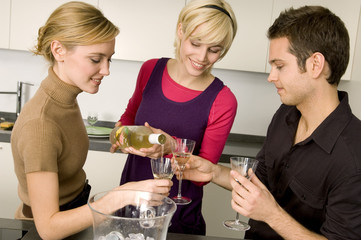 Young woman pouring wine for her friends
