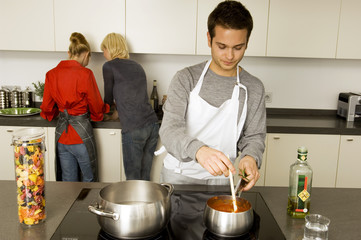 Young man cooking food with two young women standing behind him