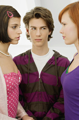 Close-up of a teenage boy standing with two young women