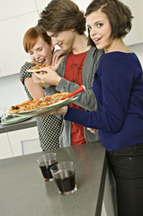 Portrait of a young woman holding a plate of pizza standing with her friends