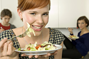 Portrait of a young woman eating salad with her friends in background