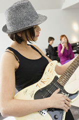 Side profile of a young woman playing a guitar