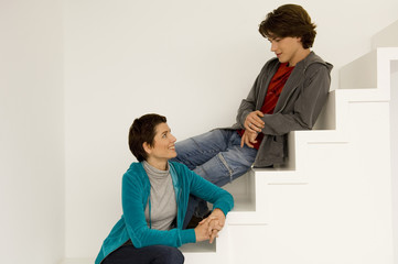 Mid adult woman and her son sitting on a staircase