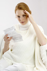 Close-up of a pregnant young woman reading a medical report