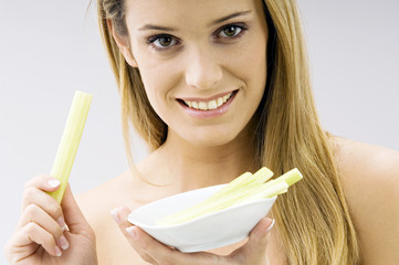 Portrait of a young woman holding celery sticks and smiling