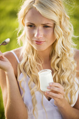 Portrait of young woman eating a yoghurt