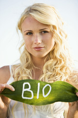 "Young woman holding a leaf with ""BIO"" lettering"