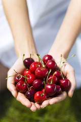 Young woman holding cherries