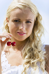 Young woman holding two cherries