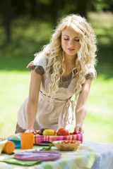 Young woman setting table outdoors