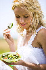Young woman eating vegetables