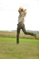Young woman running on the grass
